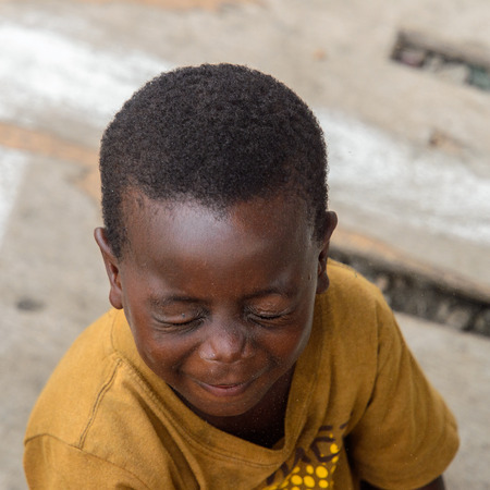 ACCRA, GHANA - JAN 8, 2017: Unidentified Ghanaian little boy in mustard shirt closes his eyes. Children of Ghana suffer of poverty due to the economic situation Editoriali