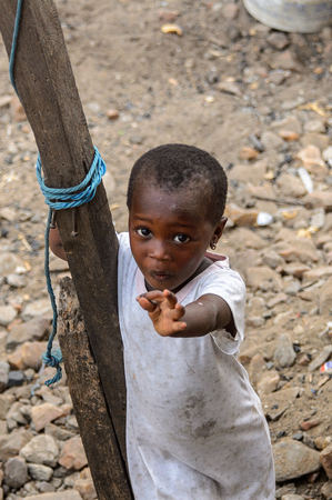 ACCRA, GHANA - JAN 8, 2017: Unidentified Ghanaian little girl in dirty white dress holds on the wooden pole. Children of Ghana suffer of poverty due to the economic situation Stock Photo - 112568162