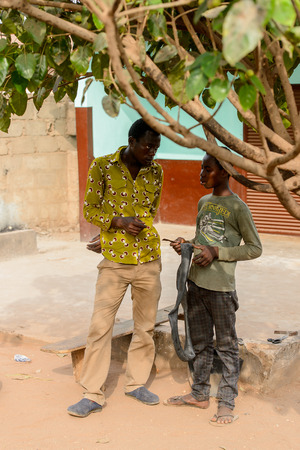 ACCRA, GHANA - JAN 8, 2017: Unidentified Ghanaian two men talk about something on the street. People of Ghana suffer of poverty due to the economic situation Editorial