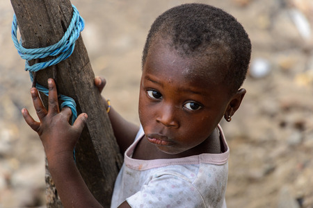 ACCRA, GHANA - JAN 8, 2017: Unidentified Ghanaian little girl in dirty white shirt holds on the wooden pole. Children of Ghana suffer of poverty due to the economic situation Stock Photo - 112568232