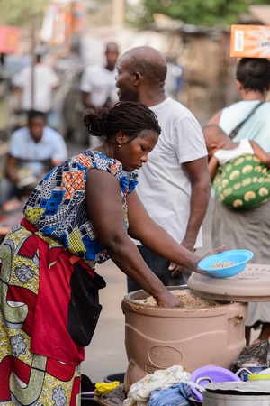 LOME, TOGO - Jan 9, 2017: Unidentified Togolese woman pours a porridge in to a bowl at the Lome central market. Togo people suffer of poverty due to the bad economy