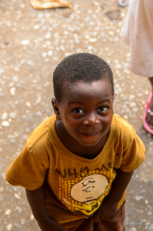 ACCRA, GHANA - JAN 8, 2017: Unidentified Ghanaian little boy in mustard shirt amazedly looks forward. Children of Ghana suffer of poverty due to the economic situation