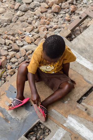 ACCRA, GHANA - JAN 8, 2017: Unidentified Ghanaian little boy in mustard shirt sits on the wooden board. Children of Ghana suffer of poverty due to the economic situation