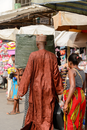 LOME, TOGO - Jan 9, 2017: Unidentified Togolese man in muslim suit from behind at the Lome central market. Togo people suffer of poverty due to the bad economy