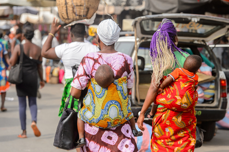 LOME, TOGO - Jan 9, 2017: Unidentified Togolese little babies carried by their mothers at the Lome central market. Togo children suffer of poverty due to the bad economy Banque d'images - 112635035