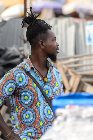 LOME, TOGO - Jan 9, 2017: Unidentified Togolese man with dreads and in colored shirt at the Lome central market. Togo people suffer of poverty due to the bad economy