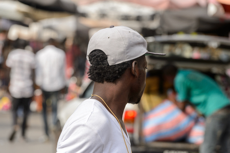 LOME, TOGO - Jan 9, 2017: Unidentified Togolese man in white shirt and hat from behind at the Lome central market. Togo people suffer of poverty due to the bad economy