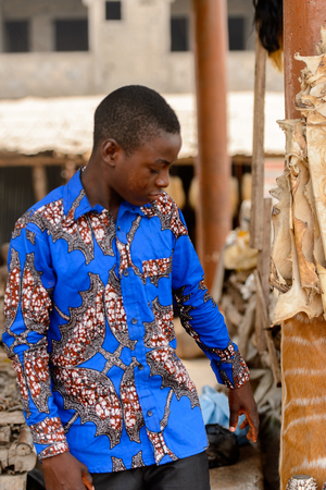 LOME, TOGO - Jan 9, 2017: Unidentified Togolese boy in blue shirt looks down at the Lome fetish market. Togo people suffer of poverty due to the bad economy