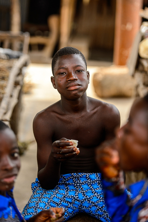 LOME, TOGO - Jan 9, 2017: Unidentified Togolese boy has his meal  at the Lome fetish market. Togo people suffer of poverty due to the bad economy Banque d'images - 112635149