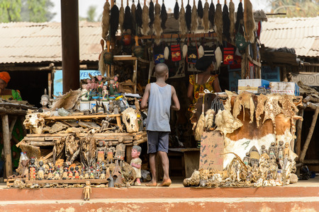LOME, TOGO - Jan 9, 2017: Unidentified Togolese young boy stands near souvenir shop at the Lome fetish market. Togo people suffer of poverty due to the bad economy Banque d'images - 112635181