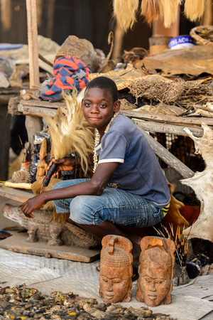 LOME, TOGO - Jan 9, 2017: Unidentified Togolese young boy sits besides the counter at the Lome fetish market. Togo people suffer of poverty due to the bad economy Editorial