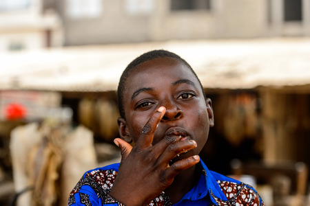 LOME, TOGO - Jan 9, 2017: Unidentified Togolese boy in blue shirt licks his fingers at the Lome market. Togo people suffer of poverty due to the bad economy