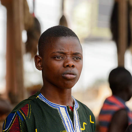 LOME, TOGO - Jan 9, 2017: Unidentified Togolese boy in green shirt surprisingly looks away at the Lome fetish market. Togo people suffer of poverty due to the bad economy
