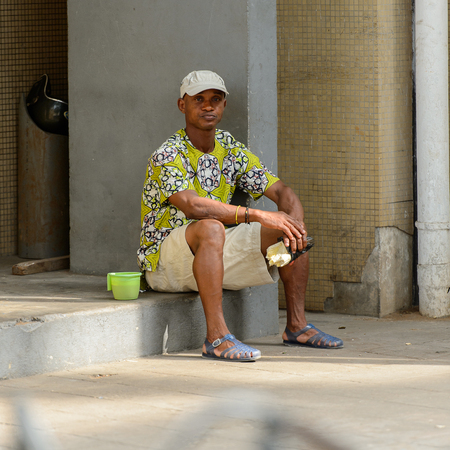 LOME, TOGO - Jan 9, 2017: Unidentified Togolese young man sits at the Lome central market. Togo people suffer of poverty due to the bad economy
