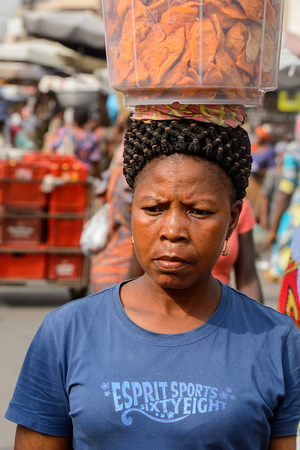 LOME, TOGO - Jan 9, 2017: Unidentified Togolese woman carries a basin on her head at the Lome central market. Togo people suffer of poverty due to the bad economy Banque d'images - 112704123