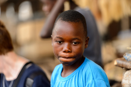 LOME, TOGO - Jan 9, 2017: Unidentified Togolese boy in blue shirt hides his lips at the Lome fetish market. Togo children suffer of poverty due to the bad economy