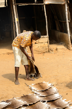 LOME, TOGO - Jan 9, 2017: Unidentified Togolese  young boy bends down to pick up his goods at the Lome fetish market. Togo people suffer of poverty due to the bad economy Imagens - 112565648