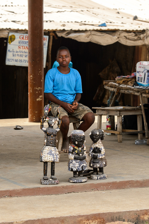 LOME, TOGO - Jan 9, 2017: Unidentified Togolese boy in blue shirt sits on the wooden chair at the Lome fetish market. Togo people suffer of poverty due to the bad economy