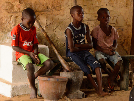 LOME, TOGO - Jan 9, 2017: Unidentified Togolese young boys sit on the wooden bench in the local shamans house. Togo children suffer of poverty due to the bad economy 報道画像