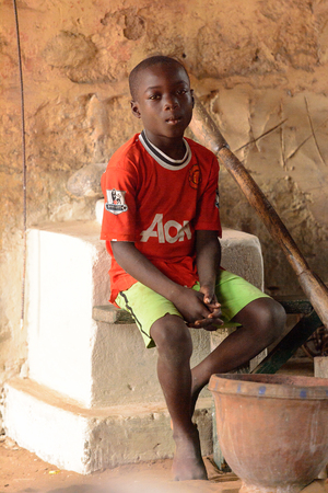 LOME, TOGO - Jan 9, 2017: Unidentified Togolese young boy in red shirt sits in the local shamans house. Togo children suffer of poverty due to the bad economy