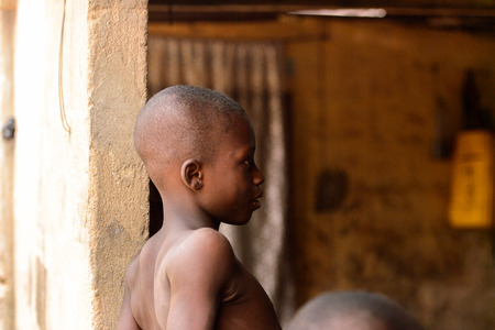 LOME, TOGO - Jan 9, 2017: Unidentified Togolese young boy in the local shaman's house. Togo people suffer of poverty due to the bad economy