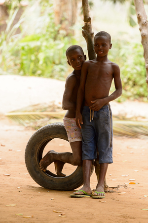 LOME, TOGO - Jan 9, 2017: Unidentified Togolese young boy sits on wheel with his friend. Togo people suffer of poverty due to the bad economy