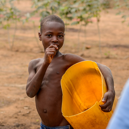 LOME, TOGO - Jan 9, 2017: Unidentified Togolese young boy holds yellow bucket. Togo children suffer of poverty due to the bad economy Editoriali