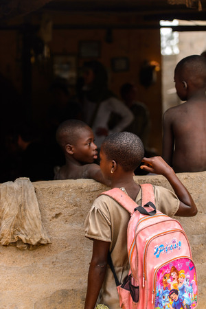 LOME, TOGO - Jan 9, 2017: Unidentified Togolese young girl carries a backpack near the local shamans house. Togo people suffer of poverty due to the bad economy Editorial