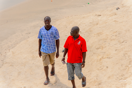 ACCRA, GHANA - Jan 8, 2017: Unidentified Ghanaian men walk along the beach at the local market. People of Ghana suffer of poverty due to the economic situation Editorial
