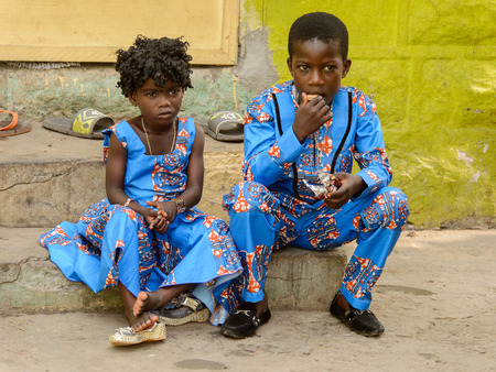 ACCRA, GHANA - Jan 8, 2017: Unidentified Ghanaian children in blue suits sit at the local market. People of Ghana suffer of poverty due to the economic situation
