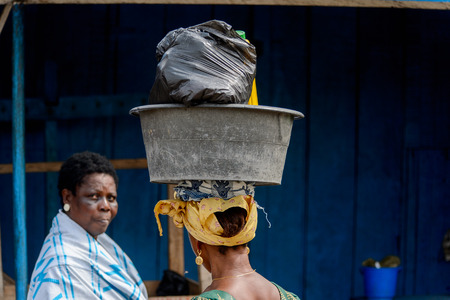 ACCRA, GHANA - Jan 8, 2017: Unidentified Ghanaian woman carries a basin at the local market. People of Ghana suffer of poverty due to the economic situation