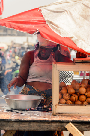 ACCRA, GHANA - Jan 8, 2017: Unidentified Ghanaian woman puts her hand into the bowl at the local market. People of Ghana suffer of poverty due to the economic situation