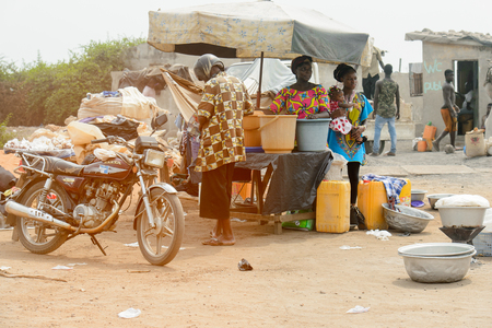 LOME, TOGO - Jan 9, 2017: Unidentified Togolese women stand behind the counter full of buckets. Togo people suffer of poverty due to the bad economy Editorial