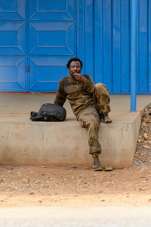 ACCRA, GHANA - Jan 8, 2017: Unidentified Ghanaian smiling man sits on the street. People of Ghana suffer of poverty due to the economic situation Stock Photo - 112568653