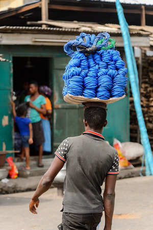 ACCRA, GHANA - Jan 8, 2017: Unidentified Ghanaian man carries a tray with ropes at the local market. People of Ghana suffer of poverty due to the economic situation