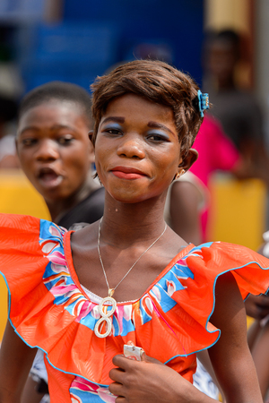 ACCRA, GHANA - Jan 8, 2017: Unidentified Ghanaian woman in red dress smiles at the local market. People of Ghana suffer of poverty due to the economic situation