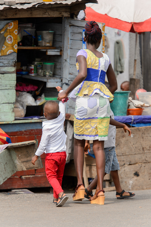 ACCRA, GHANA - Jan 8, 2017: Unidentified Ghanaian woman holds her little son for a hand at the local market. People of Ghana suffer of poverty due to the economic situation