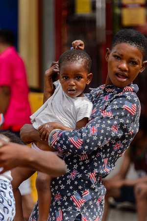 ACCRA, GHANA - Jan 8, 2017: Unidentified Ghanaian woman carries a little girl in her hands at the local market. People of Ghana suffer of poverty due to the economic situation