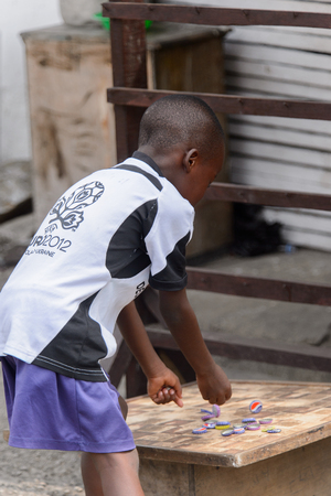 ACCRA, GHANA - Jan 8, 2017: Unidentified Ghanaian little boy plays with caps at the local market. People of Ghana suffer of poverty due to the economic situation Editorial