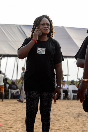OUIDAH, BENIN - Jan 10, 2017: Unidentified Beninese young girl in black shirt and pants works at the voodoo festival, which is anually celebrated on January, 10th. Editorial