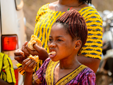 OUIDAH, BENIN - Jan 10, 2017: Unidentified Beninese girl in colored dress chews bread. Benin people suffer of poverty due to the bad economy