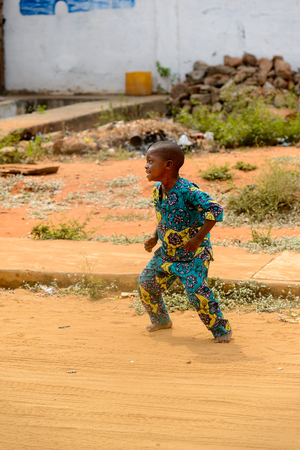 OUIDAH, BENIN - Jan 10, 2017: Unidentified Beninese barefoot boy in colored suit gets ready to run. Benin children suffer of poverty due to the bad economy Stock Photo - 114311147