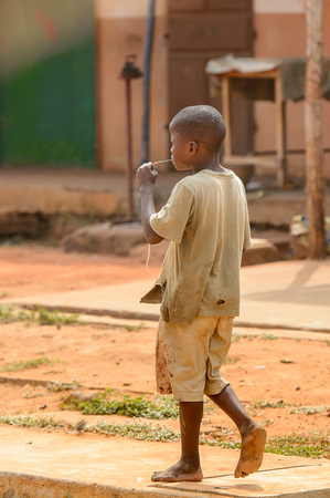 OUIDAH, BENIN - Jan 10, 2017: Unidentified Beninese barefoot boy in dirty clothes from behind. Benin children suffer of poverty due to the bad economy