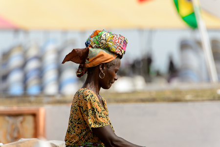 OUIDAH, BENIN - Jan 10, 2017: Unidentified Beninese woman in colored clothes and headscarf walks on the street. Benin people suffer of poverty due to the bad economy 報道画像