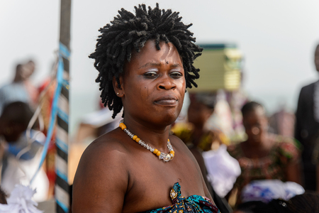 OUIDAH, BENIN - Jan 10, 2017: Unidentified Beninese woman with dreads wears necklace and earings at the voodoo festival, which is anually celebrated on January, 10th.