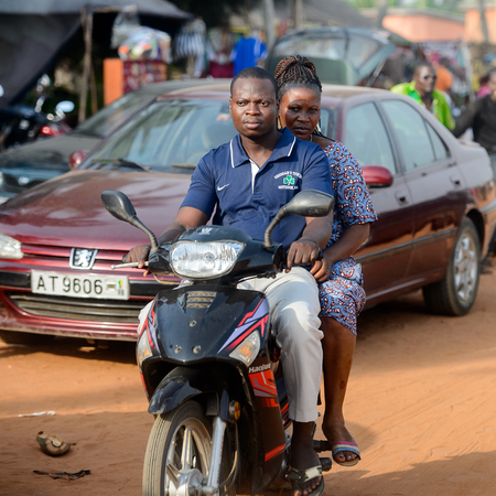 OUIDAH, BENIN - Jan 10, 2017: Unidentified Beninese man rides a motorcycle at the local market. Benin people suffer of poverty due to the bad economy Editorial