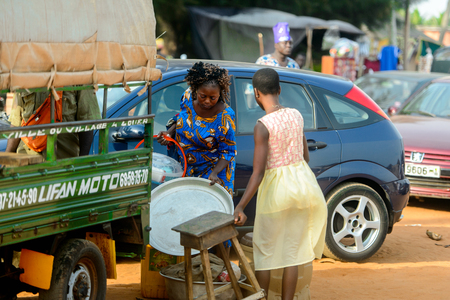OUIDAH, BENIN - Jan 10, 2017: Unidentified Beninese woman holds on the wooden chair at the local market. Benin people suffer of poverty due to the bad economy