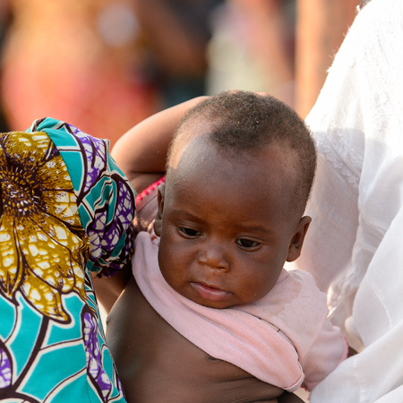 OUIDAH, BENIN - Jan 10, 2017: Unidentified Beninese little baby in pink shirt looks down at the local market. Benin children suffer of poverty due to the bad economy Editorial