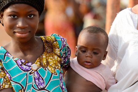 OUIDAH, BENIN - Jan 10, 2017: Unidentified Beninese beautiful woman smiles and holds her little baby at the local market. Benin people suffer of poverty due to the bad economy Sajtókép