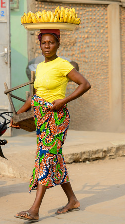 OUIDAH, BENIN - Jan 10, 2017: Unidentified Beninese woman carries a tray on the street. Benin people suffer of poverty due to the bad economy